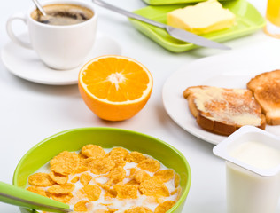 breakfast with cornflakes, two toasts, an orange and coffee