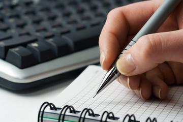 Businesswoman writing.