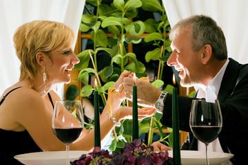Mann und Frau füttern sich mit Pasta