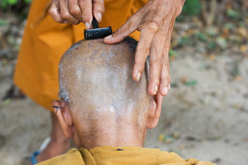 monk getting head shaved by fellow monk