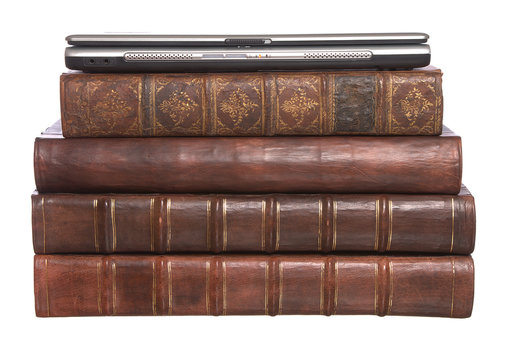 Pile of old leather bound books with a laptop