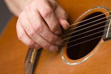 Acoustic guitar player using plectrum