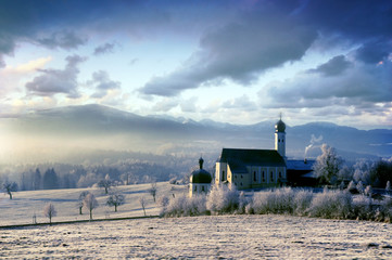 Alpine scenery with church in the frosty morning
