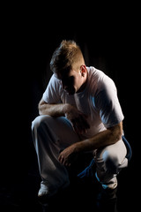 Lifestyle portrait of young man in crouching pose in dark