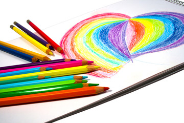 Crayons and heart on notebook