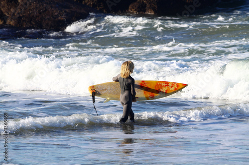 jeune enfant sur la plage avec une planche de surf photo. Black Bedroom Furniture Sets. Home Design Ideas
