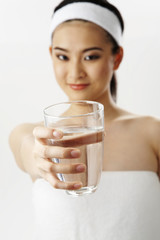 woman in towel show a glass of water
