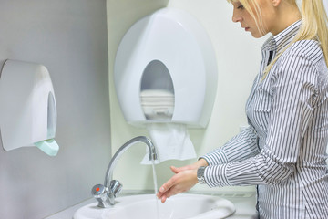 blue hair woman washing hands in restroom