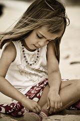 fillette fermant sa chaussure - couleurs délavées