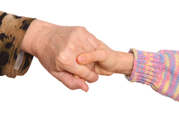 Grandmother and granddaughter hold hands.
