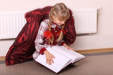 Girl lie on floor near radiator with book.