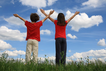 Kids holding arms up in praise against blue sky