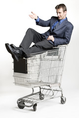 Businessman sitting on a shopping cart