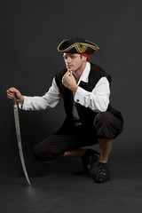 serious pirate with sabre sitting