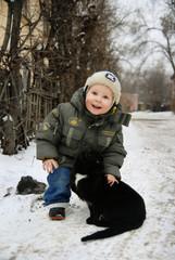Smiled little boy stroking the black cat