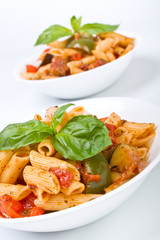 two servings of of mediterranean pasta in white bowls