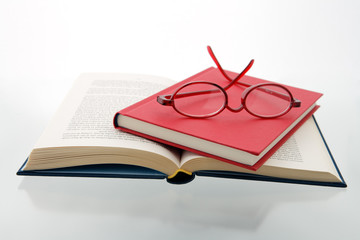 red blue books reading glasses  reflecting white surface