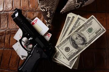 Dollar notes and gun, black pistol
