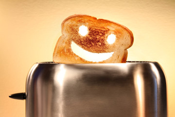 Toast with smiley face in toaster  on counter