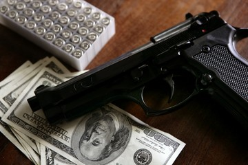 Dollar notes and gun, black pistol