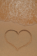 Heart drawing on sandy beach