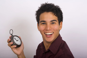 A young Asian American man holds a clock in his hands