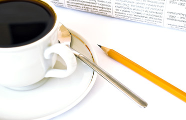 Cup of coffee and newspaper on white