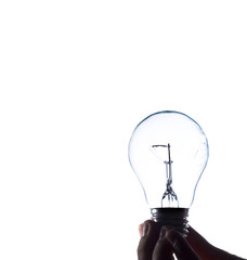 A little hand holds an electric light bulb