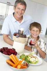Father And Son Making Fresh Vegetable Juice
