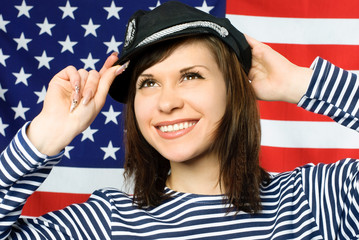 beautiful sailor standing near the American flag