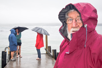 Grandfather and family walking in rain