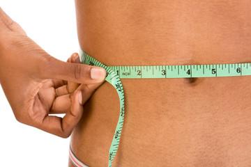 Measuring waist, close up of ethnic woman abdomen
