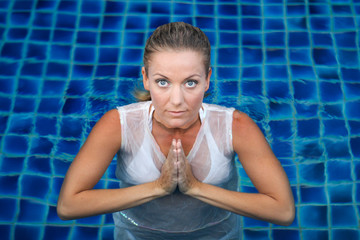 gorgeous blond woman doing yoga in the pool.