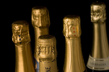 A group of champagne bottles. Shot of the top part of the foil