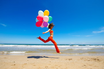 young woman with colorful balloons running on the beach