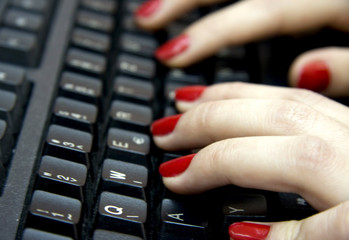 Computer keyboard and woman fingers typing on it