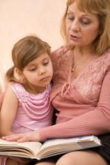 Grandchild and grandmother read book