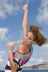 fun blonde girl with lollipop in clouds and blue background