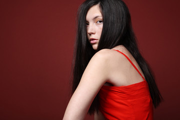 Brunette posing in red dress.
