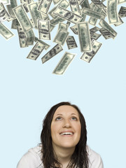 hundred dollar bills starting to rain on happy woman
