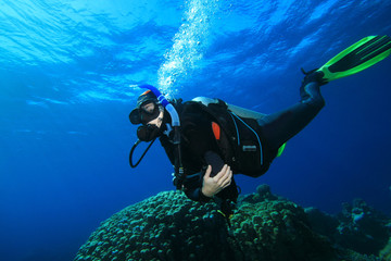 Woman Scuba Diver swims over Coral Reef