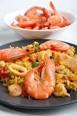 Spanish paella on a dark plate with king shrimps