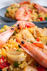 two servings of Spanish paella on dark plates with king shrimps