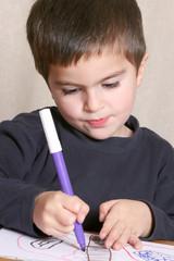 bambino che disegna con pennarello