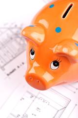 Sparschwein auf Bauplänen