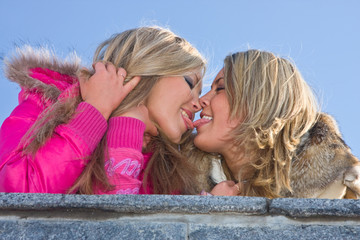 Two girlfriends blondes kiss on blue sky background