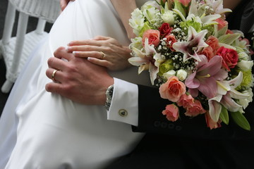 wedding rings on hands and flowers