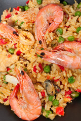 Spanish paella in a dark pan