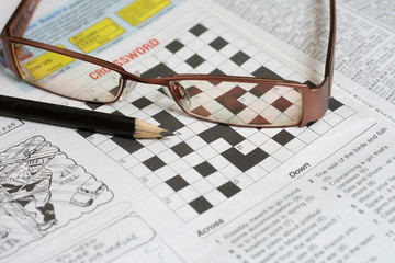 Pencil, glass and a crossword puzzle