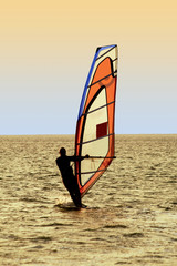 Silhouette of a windsurfer on waves of a sea